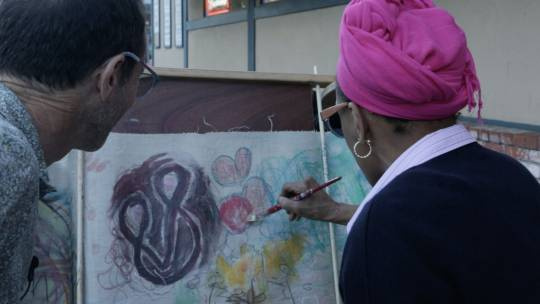 A woman paints on the Curious Scroll while remembering how her community came together in the face of violence.